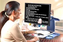 A woman uses the TOPAZ XL HD Freeze Frame feature to follow the text of a recipe