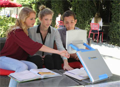 Students in an outdoor courtyard using the TOPAZ PHD portable video magnifier to study