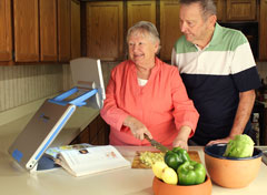 Woman and man making a salad while using the TOPAZ PHD to magnify a recipe in a cookbook